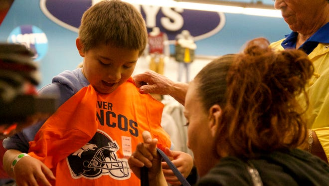 Juan Chavez, 10, and his mother, Holly Dominguez, pick out Denver Broncos T-shirts during Dress the Child event earlier this month at Old Navy in Las Cruces.