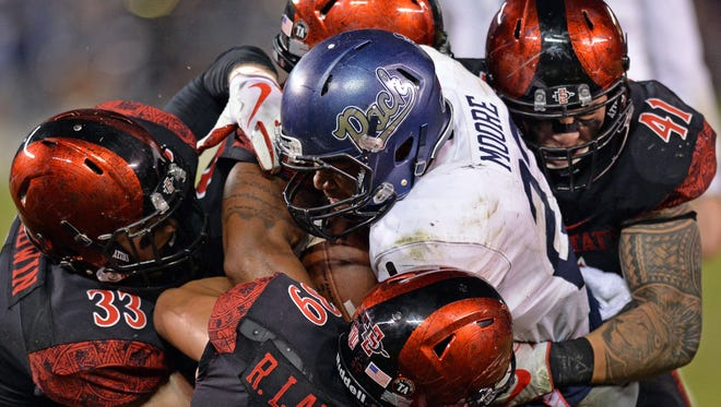 Wolf Pack running back Kelton Moore is tackled by a host of San Diego State players last season.