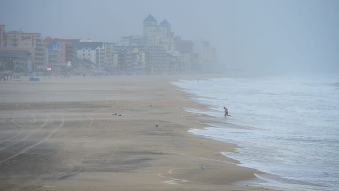 """A person runs out of the water where he was attempting to swim in the rough surf during what is being called """"Potential Tropical Cyclone 10"""" in Ocean City, Md. on Tuesday, August 29, 2017."""