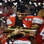 Ohio State Buckeyes wide receiver Devin Smith (9) cradles the trophy after their win over the Oregon Ducks in the 2015 CFP National Championship Game at AT&T Stadium.