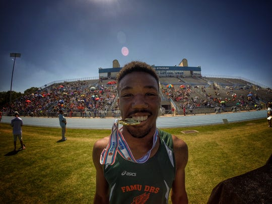 FAMU DRS junior Chris Jackson celebrates his state title in the 110-meter hurdles in May by chomping on his gold medal.