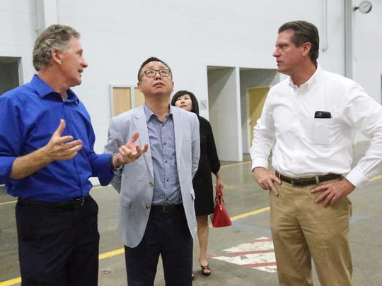 Brett Preston, left, and David Hingst, right, both of Cushman & Wakefield/Pires International real estate firm talk with Daejae Kim, center, director of the Korean American-Apparel Manufacturers Association inside the former Hoover plant in West El Paso Tuesday.