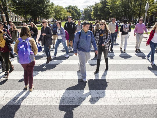 University of Delaware students cross the street at East Delaware Avenue on Monday afternoon.