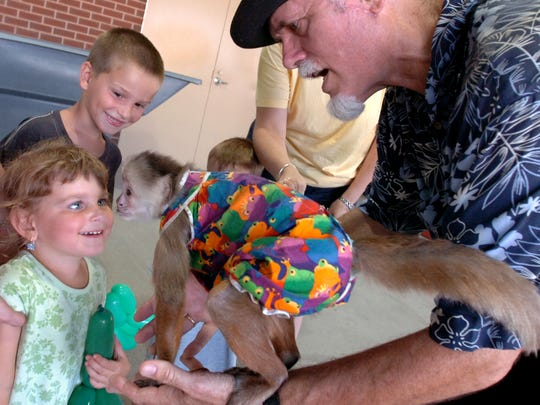 In this file photo, Ava Michalski, 3, gets a kiss from Django the monkey at a Monkey Magic Mondays promotion in 2007.