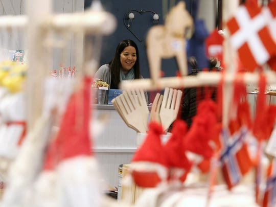 Kristin Klassert is framed by various nordic-themed ornaments as she helps a customer at Nordiska in Poulsbo.