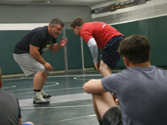 Former Lexington wrestling coach Brent Rastetter demonstrates a move with the help of fellow Madison alum Gavin Speelman during Madison's Champ Camp on Thursday night. Rastetter is starting a wrestling program at Otterbein University from scratch.