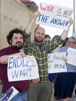 Lucas Herndon, left, and Peter Sloan,  both of Las Cruces stand near the Federal Courthouse in downtown Las Cruces on Friday, April 7, 2017, to protest President Donald Trump's decision to attack Syria the night before. The protest was organized by Las Cruces Unified Community Action.