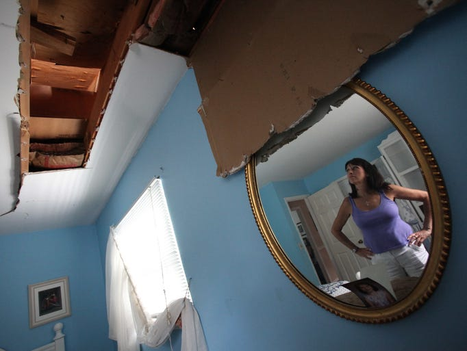 Janet Barry of Cortlandt, reflected in a mirror, looks at the damage caused from a fallen tree to her mother's bedroom. Overnight winds and heavy rain uprooted a large oak tree at her mother's home in Montrose, causing extensive damage to the roof and side of the two story home on Meadow Road. According to Barry, 'Thank God, my mother  was away visiting friends in South Carolina and no one was home.' No injuries were reported in the incident.