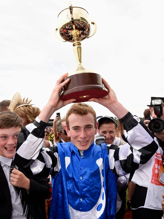 Jockey Ryan Moore celebrates with the trophy after winning with German horse Protectionist in the Melbourne Cup horse racing at the Flemington Racecourse in Melbourne, Australia, Tuesday, Nov. 4, 2014. (AP Photo/Andy Brownbill)