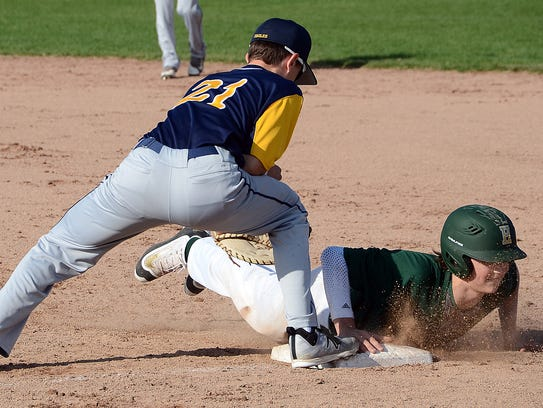 Howell's Luke Russo dives back into first base before