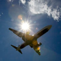 In this July 20, 2009 file photo, a plane flies into Portland International Airport in Oregon.