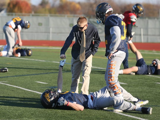 Football team manager Zac Houliares, center in glasses, gets a fist bump from Matt Gardner during stretching at the start of practice at Victor High School Thursday, Nov. 17, 2016 in Victor.