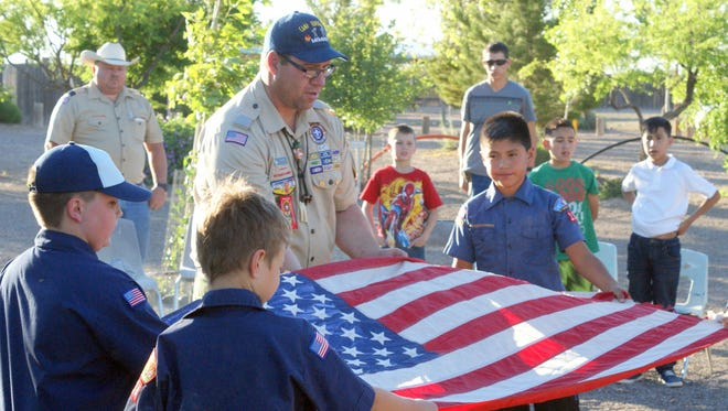 Troy Wertz helps Deming Cub Scouts with the flag retirement ceremony.