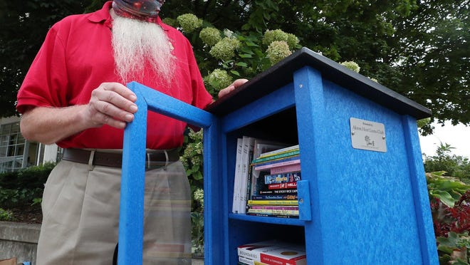 Jim Stein of the Akron Lions Club talks about the Little Library outside the Harold K. Stubbs Justice Center on Friday.