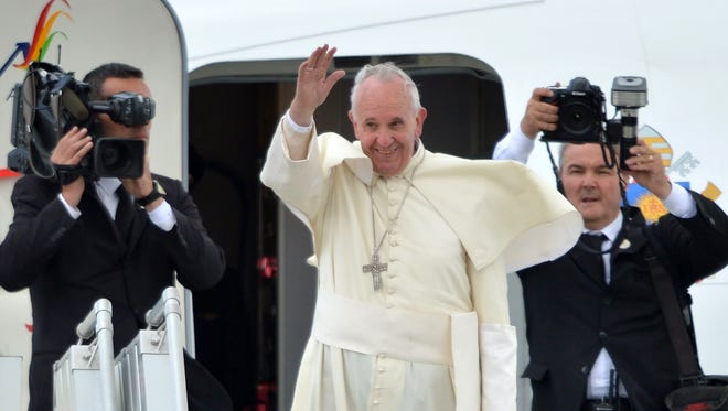 Pope Francis waves before boarding a plane bound for Bolivia, at Quito's airport on July 8, 2015.