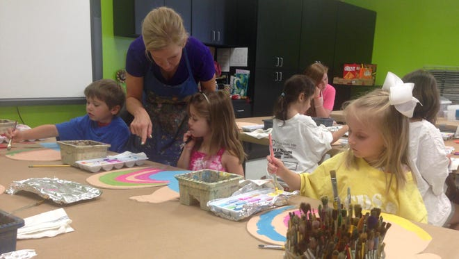 Alexandria Country Day School art teacher Penny Abraham guides campers Colin Parrish (far left, blue shirt), Sloane Marks (center) and Sophia Reish at the school's annual summer art camp on Monday.