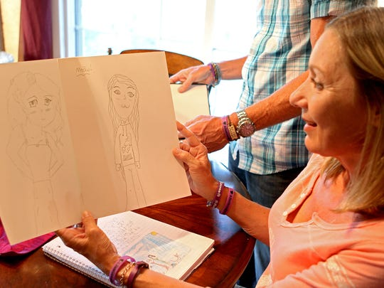Bianka Landavazo looks over drawings done by her daugher, Lauren, while going through old scrapbooks on Aug. 28.