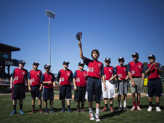 Red Land Little League team member Jaden Henline tips his cap as the team is introduced to the crowd. Little League World Series U.S. champions Red Land are honored prior to the York Revolution's final game of the season against the Somerset Patriots at Santander Stadium in Yrork, Sunday, September 20, 2015.