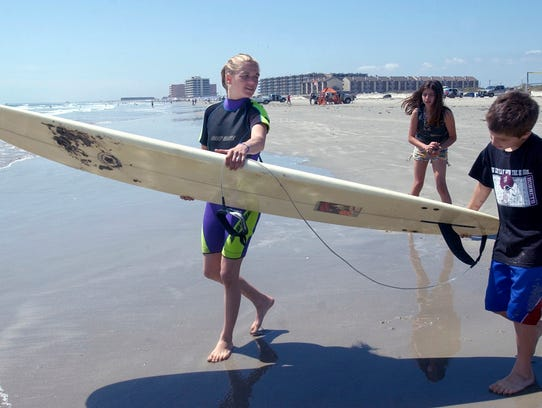Kristian Baril, 8, of Corpus Christi; helps her mother Monique Baril carry her surboard into the water during spring break 2008 on Padre Island. Texas Beach Watch's website says all local beaches have safe levels of fecal bacteria. A few area beaches had high levels after testing early last week.