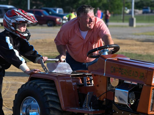 "Competing in the stock altered class, Jim Thompson from Greensburg, Indiana, helps his son Tyler Thompson, 12, push their tractor ""Copperhead Jr."" up to the pulling sled during the Garden Tractor Pulls at the Henderson County Fairgrounds on Saturday."
