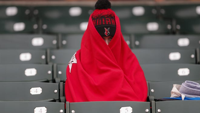Indianapolis Indians fans attempt to stay warm before the start of their game on opening night at Victory Field on Friday, April 6, 2018.