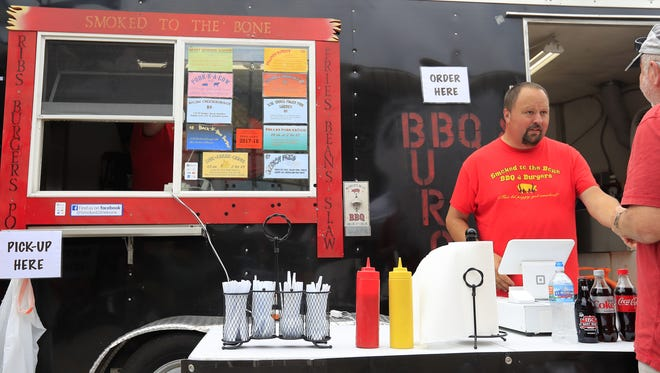 Jeff Ellis takes an order at his Smoked to the Bone food truck Wednesday at the Farmers Market on Broadway. It's a family venture for Jeff, wife Kim and their kids, Andrew and Victoria.