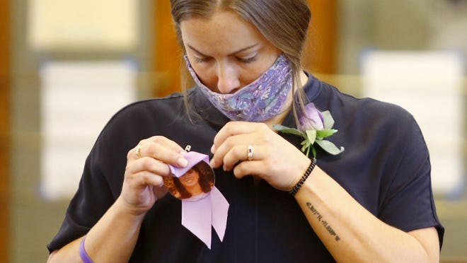 Julianna Melchionda pins a ribbon and photo of her mother Laurie in a courtroom on Sept. 10, 2020.