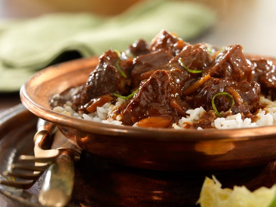 Pork cubes are braised in beer and cider, then stirred with mole sauce made using Mexican chocolate and served over hot rice.
