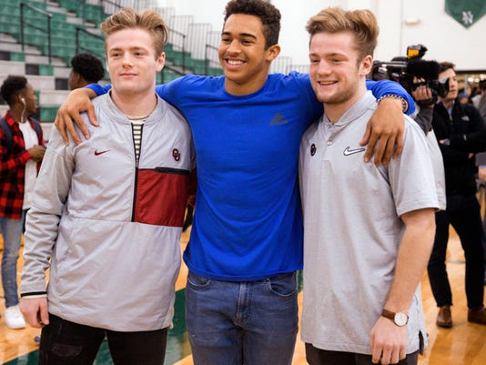 CORRECTS TO FORMER OKLAHOMA HEAD COACH BOB STOOPS - Norman North's Ryan Peoples, center, poses for a photo with Drake, left, and Issac Stoops, after signing his letter of intent to play football for Northeastern Oklahoma University during national signing day at Norman North High School in Norman, Okla., Wednesday, Feb. 7, 2018. The Stoops brothers, twin sons of former Oklahoma head coach Bob Stoops, will be preferred walk-ons to play football for the University of Oklahoma. (Chris Landsberger/The Oklahoman via AP)