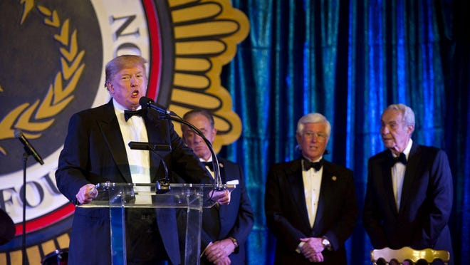 President Donald Trump stops in the ballroom to speak during The Palm Beach Police & Fire Foundation Palm Beach Policemen's and Firemen's Ball  at the Mar-a-Lago Club on Saturday, Jan. 18, 2020, in Palm Beach.