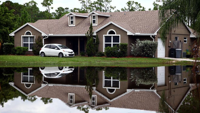 A car is parked close to the highest point of a yard off of 60th Street North in Loxahatchee after flooding caused by Tropical Storm Isaac on Aug. 30, 2012.