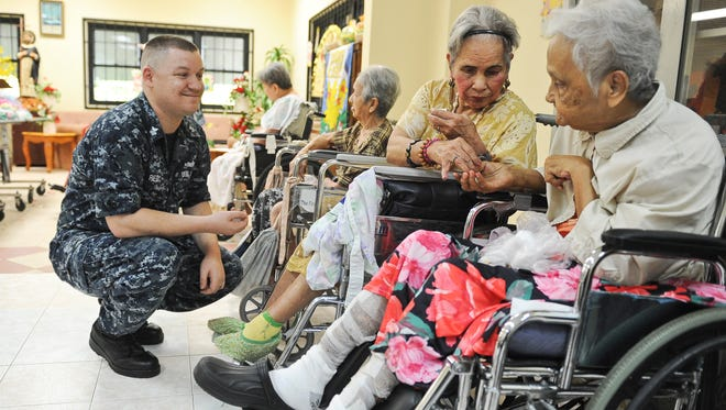 In this March 29, 2016, file photo, Petty Officer 1st Class Aric Reid, left, with St. Dominic's Senior Care Home residents Carmela Babauta, center, and Maria Babauta after  an Easter egg hunt at the facility.