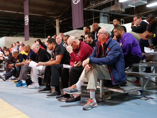 College coaches look on as athletes compete in the