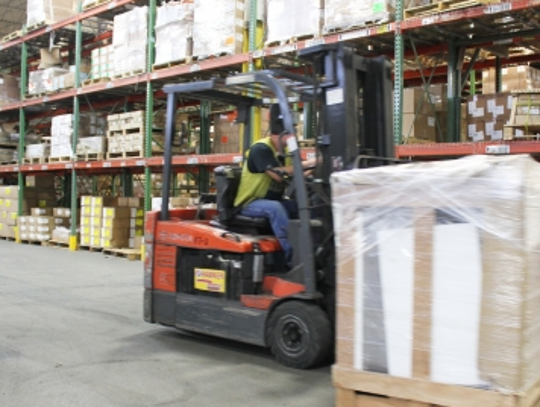 A worker uses a forklift to transport one of the donated