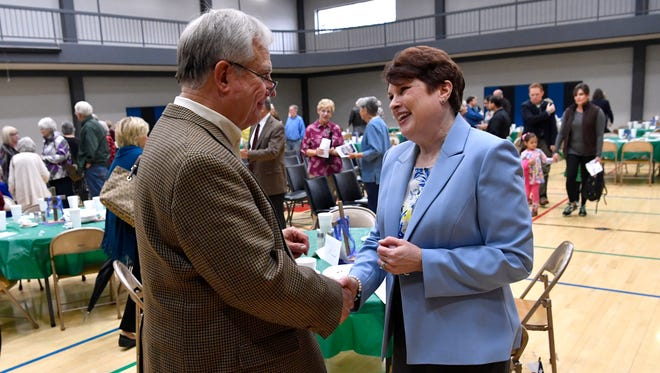 Susan Payne, interim minister at First Christian Church, shakes hands with Phil Christopher at Wednesday's Holy Week Service at First Baptist Church.