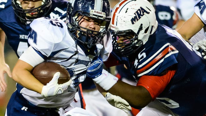 Jackson Academy's Davis McGee (39) is tackled by MRA's Saadiq Charles(45) Friday in Madison.
