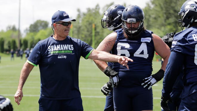 New Seahawks offensive line coach Mike Solari, left, works with offensive guard Jordan Roos (64) and others during an offseason workout this week. Solari's style emphasizes more straight-ahead blocking, as opposed to the zone blocking scheme favored by his predecessor, Tom Cable.