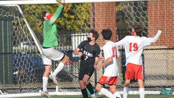 Hingham goalkeeper Jackson Price leaps high to grab a Marshfield shot as the Rams' Logan Burns, second from left, and Hingham players Brian Dalimonte as well as Curtis Murphy move into the action.