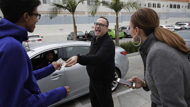 Father Jim Sichko, center, gives Nicholas Vadi, left, a $100 bill to congratulate his birthday while buying lunch for customers at an In-N-Out Burger, in the Hollywood section of Los Angeles. )