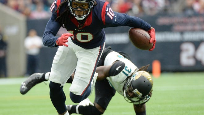 Houston Texans wide receiver DeAndre Hopkins (10) escapes the tackle of Jacksonville Jaguars cornerback Davon House (31) during the first half of an NFL football game Sunday, Jan. 3, 2016, in Houston. (AP Photo/George Bridges)