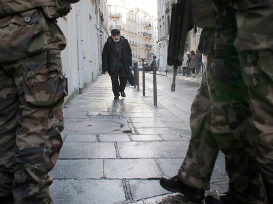 Soldiers patrol a street in Paris, Wednesday, Jan. 14, 2015. France ordered 10,000 troops into the streets Monday to protect sensitive sites — nearly half of them to guard Jewish schools — as it hunted for accomplices to the Islamic militants who left 17 people dead as they terrorized the nation.