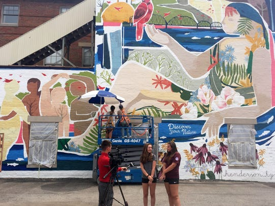 A reporter from WFIE TV interviews Haley Owens and Aiyana Mason Sunday as (on lift) muralist Leah Tumerman and Henderson artist and assistant Maddy Fritz apply sealer to the artwork.