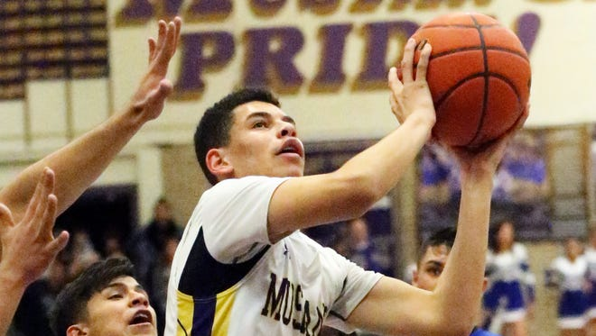 Deion Bauman, 1, of Burges gets past Joseph Gutierrez of Bowie for a shot attempt during a previous game at Burges. The Mustangs hung on against a tenacious Bear team 86-79.