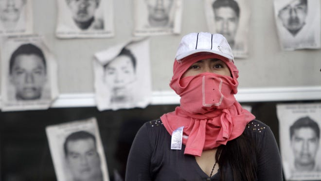 A hooded student is seen in front of the portraits of some of the 43 missing students at the tollbooths on the Chilpancingo-Acapulco highway during a protest in Chilpancingo, Guerrero State, Mexico, on Nov. 12, 2014.