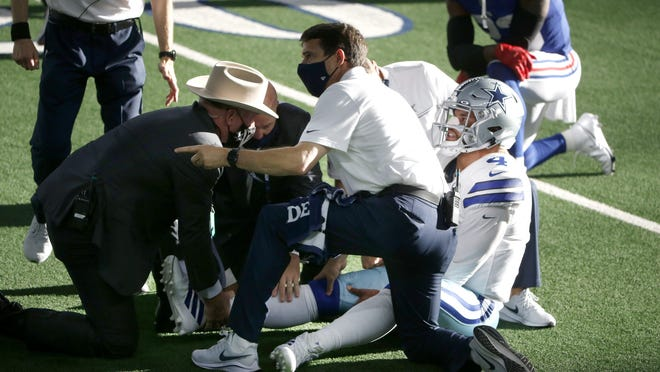 Dallas quarterback Dak Prescott is helped by first responders and team medical personnel after suffering a gruesome ankle injury during the win Sunday over the New York Giants.