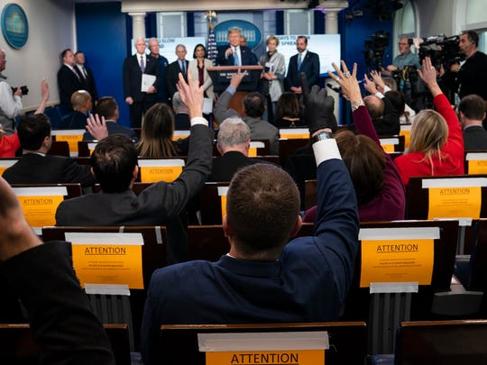 Reporters raise their hands to ask President Donald Trump a question during a press briefing with the coronavirus task force at the White House on Monday.