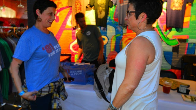 """Ashley Black, left, of Colchester tries on an '81 Bernie for Mayor T-shirt as Shelby Ferland of Colchester looks on at the Bern Down for What? fundraiser for Democratic presidential candidate Bernie Sanders on Wednesday at ArtsRiot in Burlington. Phill Landry of Unknown Arts said he was going for a """"faux vintage line"""" in creating the T-shirt that references Sanders' run for mayor of Burlington."""