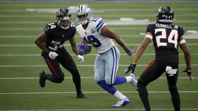 Dallas Cowboys wide receiver Amari Cooper  advances the ball after a reception while Atlanta Falcons defensive back Darqueze Dennard (left) and cornerback A.J. Terrell attempt a stop during the first half of an NFL football game in Arlington, Texas, Sunday. Dallas won 40-39.