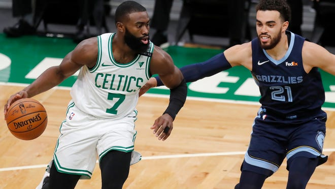 Boston Celtics' Jaylen Brown (7) drives past the Memphis Grizzlies' Tyus Jones (21) during the first half of Wednesday's game in Boston. [Michael Dwyer/The Associated Press]