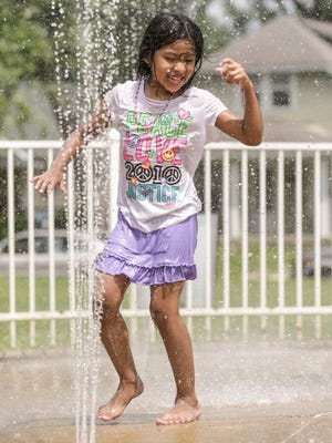 To beat the heat, Sarahe Vasquez plays in the water at the Arsenal Park splash zone, 1400 46th St., Wednesday July 20th, 2016. at Arsenal Park, 1400 46th St., Wednesday July 20th, 2016.